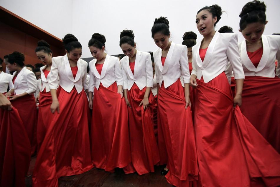 Participants check their outfit as they wait before a revolutionary song singing competition to celebrate the upcoming 90th anniversary of the founding of the Communist Party of China, in Chongqing