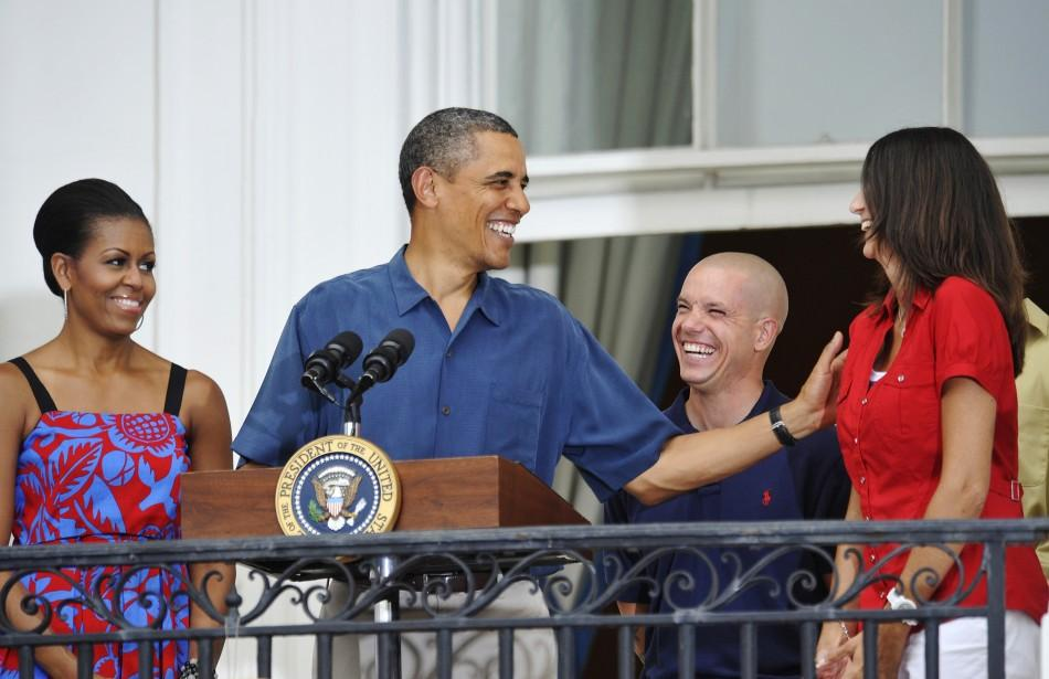 Obama and his wife Michelle smile with U.S. servicemen as he addresses an Independence Day barbeque at the White House in Washington
