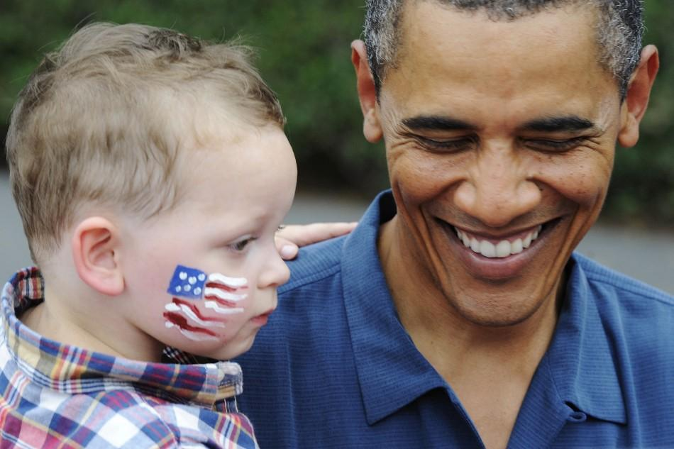 Obama holds a toddler at an Independence Day barbeque for members of the military at the White House in Washington