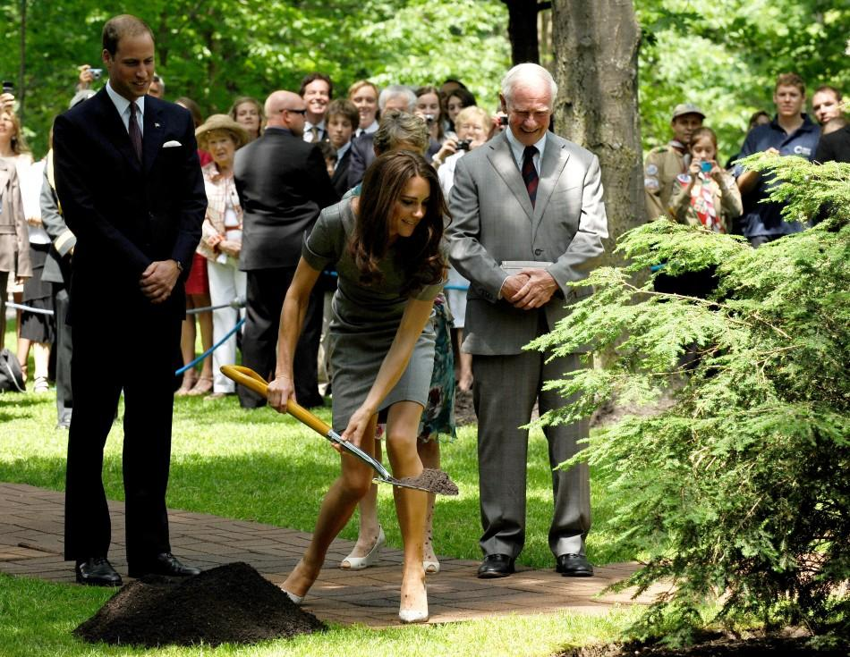Britain's Prince William (L) watches as his wife Catherine, Duchess of Cambridge wields a shovel to plant a tree at Rideau Hall in Ottawa July 2, 2011