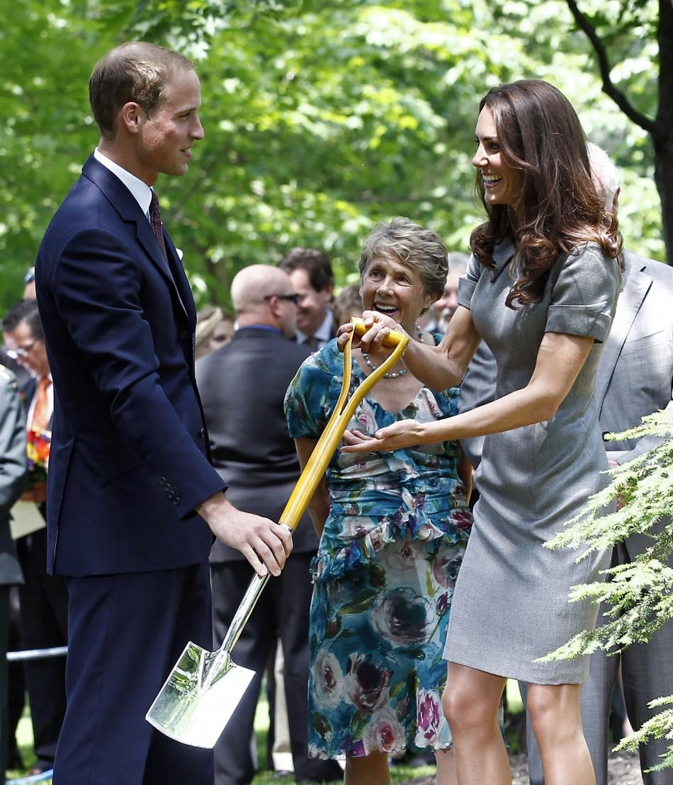 Britain's Prince William hands his wife Catherine, Duchess of Cambridge, a shovel during a tree planting ceremony at Rideau Hall in Ottawa July 2, 2011.