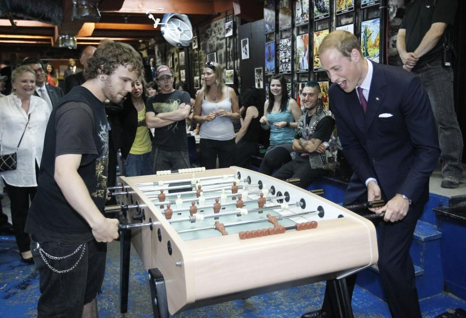 Britain's Prince William plays table soccer during a tour of the Maison Dauphine in Quebec City July 3, 2011.