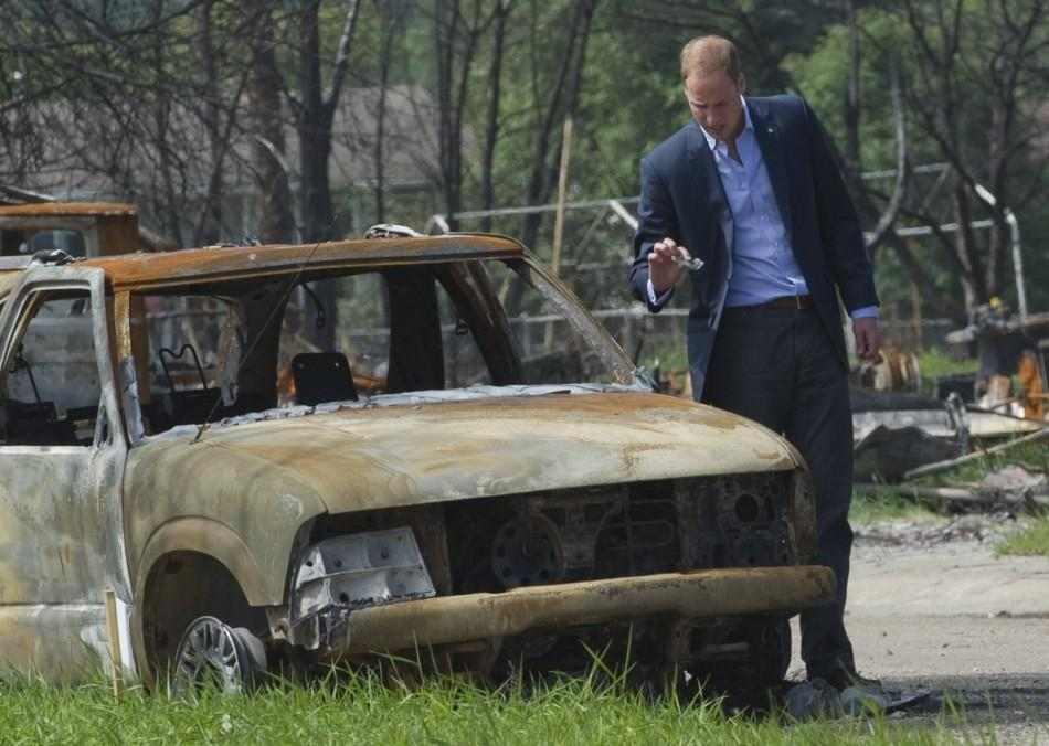Britain's Prince William looks at the damage caused by a forest fire in Slave Lake, Alberta
