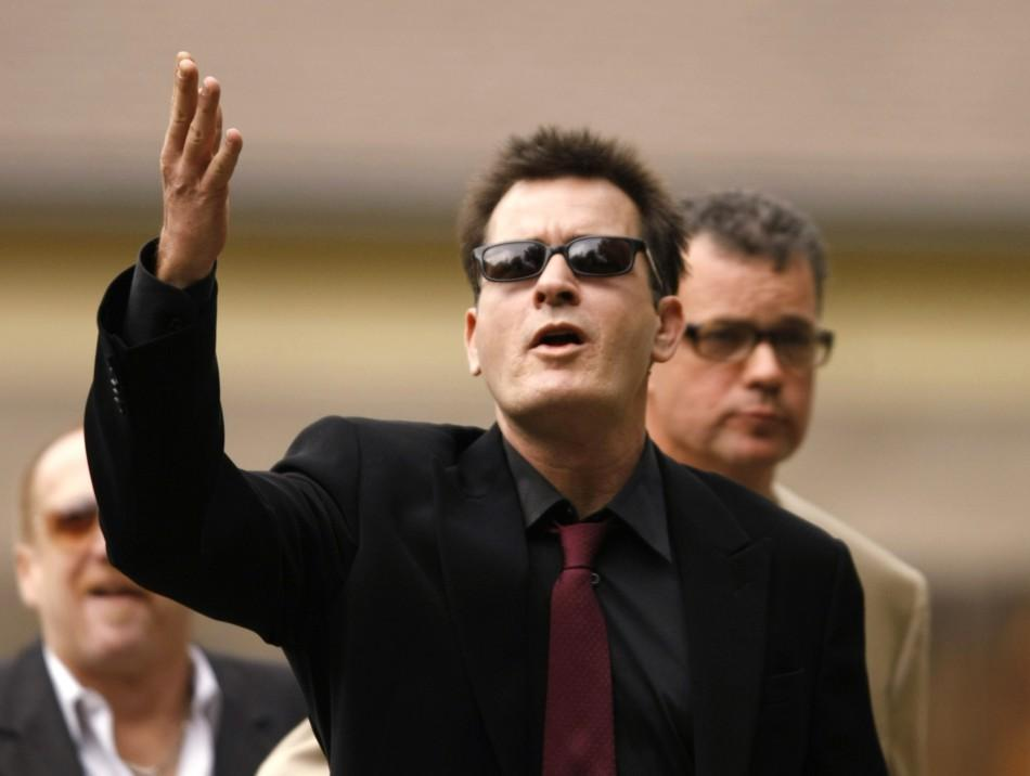 Actor Charlie Sheen gestures towards fans as he arrives for a sentencing hearing at the Pitkin County Courthouse in Aspen