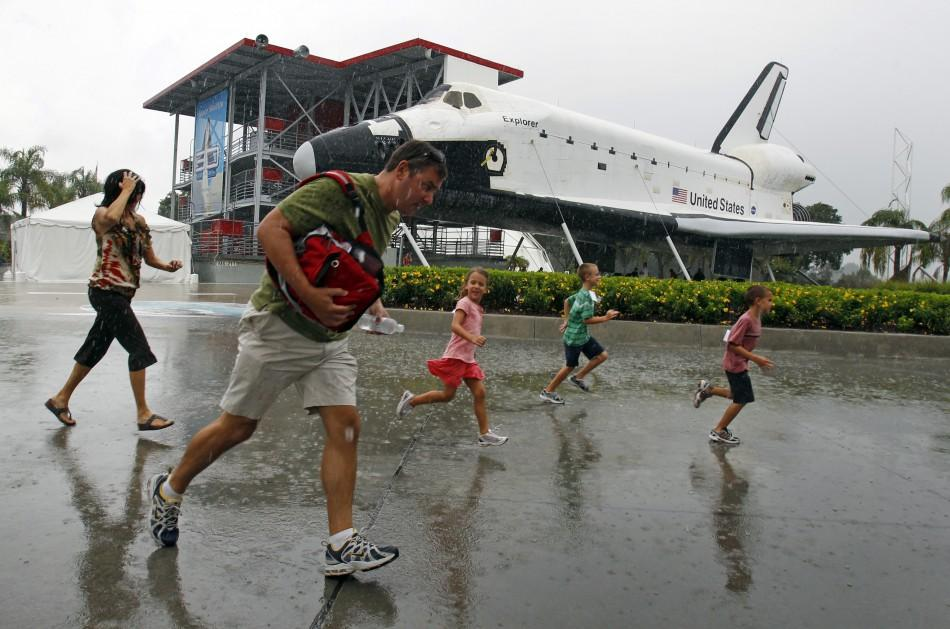 Visitors run for cover from the rain at the Kennedy Space Visitor Center Complex near Cape Canaveral