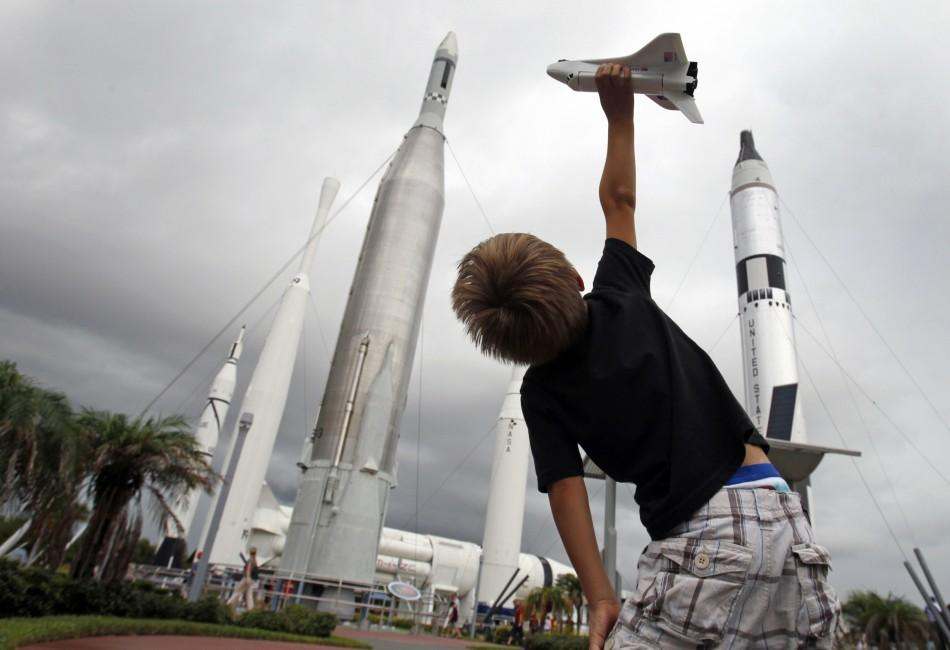 Freddy Porter of Raleigh N.C. plays with a toy space shuttle in the Rocket Garden of the Kennedy Space Center Visitor Complex