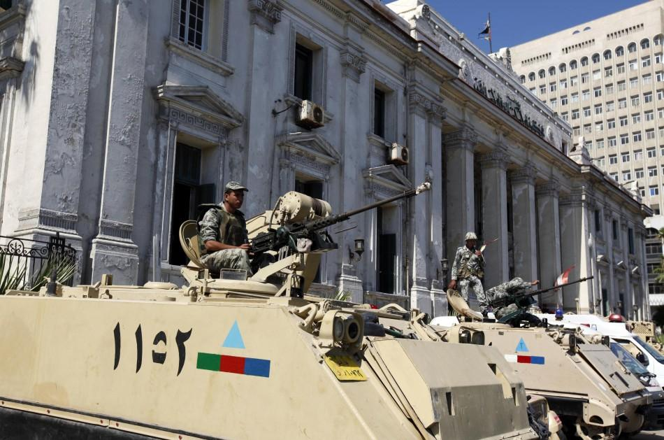 Soldiers atop armoured vehicles stand guard outside court building during trial of two police officers charged with caus...