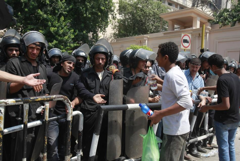 Protesters give vinegar to riot police members in front of the Interior Ministry after clashing with riot police with st...