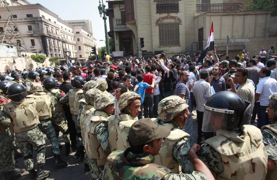 Members of the Army step in to push protesters far from the Interior Ministry after clashes between protesters and riot