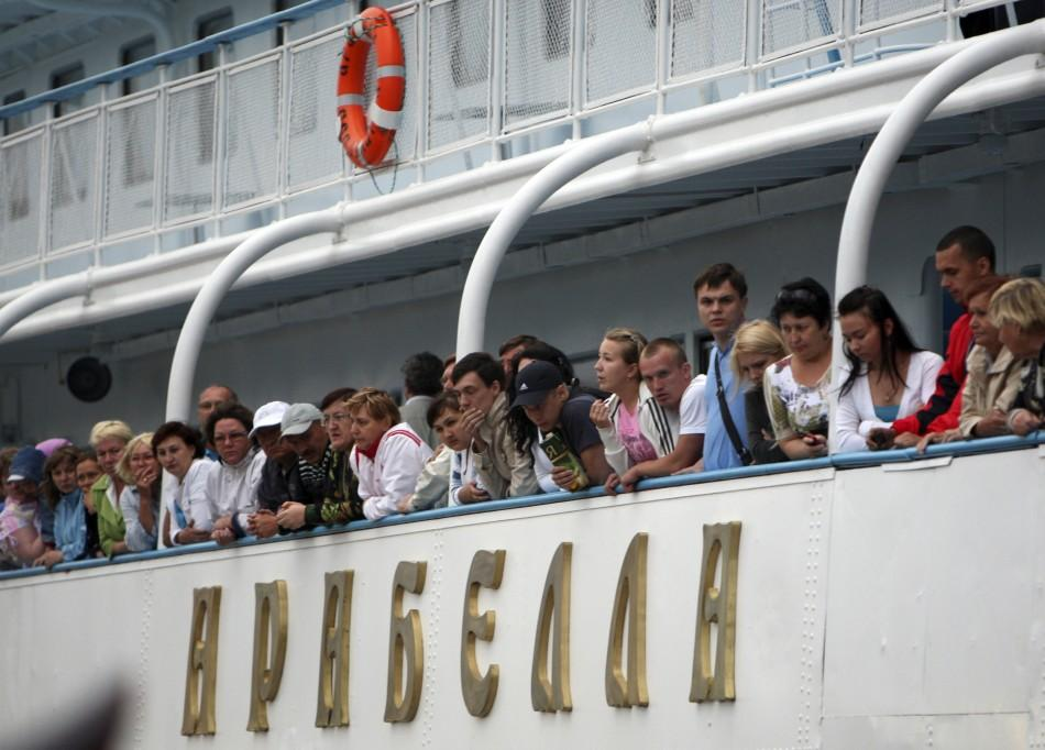 Passengers onboard the Arabella motor ship look out from the deck, after the ship rescued survivors from the Bulgaria tourist boat, at the port of Kazan