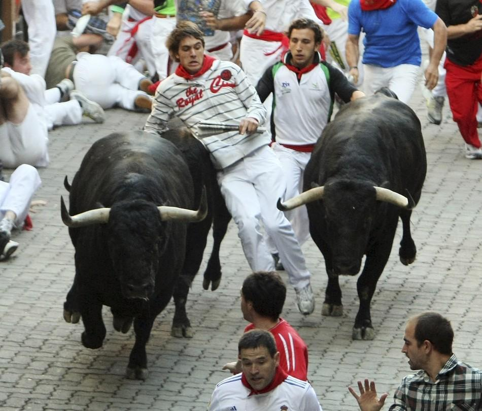 A runner is caught in between two Victoriano del Rio fighting bulls at the entrance to the bullring during the sixth running of the bulls at the San Fermin festival in Pamplona