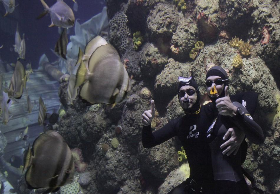 Free divers Maric and Bonin pose for a photo as they celebrate after setting the world record for the longest underwater kiss, in an oceanic tank at the Gardaland Sea Life Aquarium in Castelnuovo del Garda