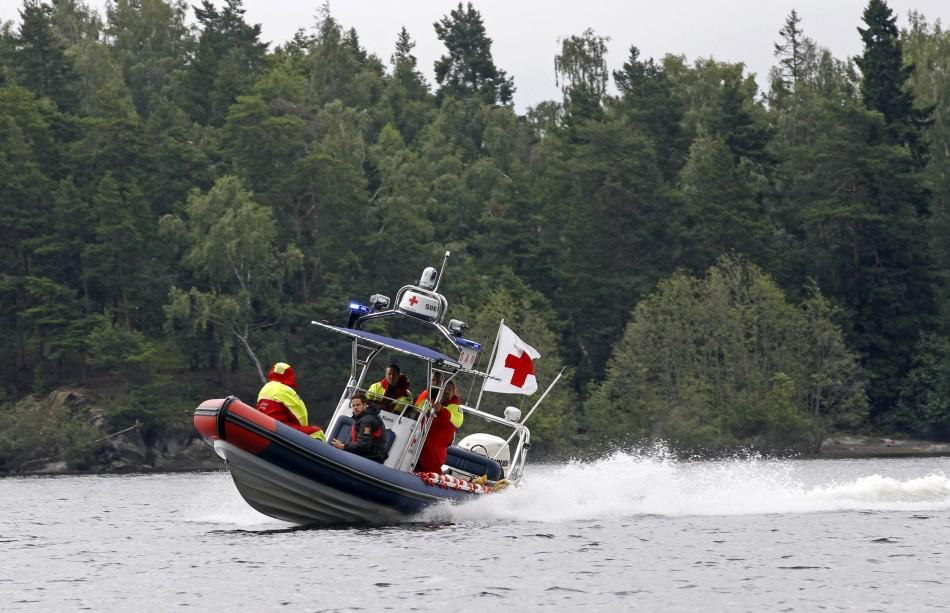 A Red Cross boat prevents the media from getting close to the shore of the small, wooded island of Utoeya