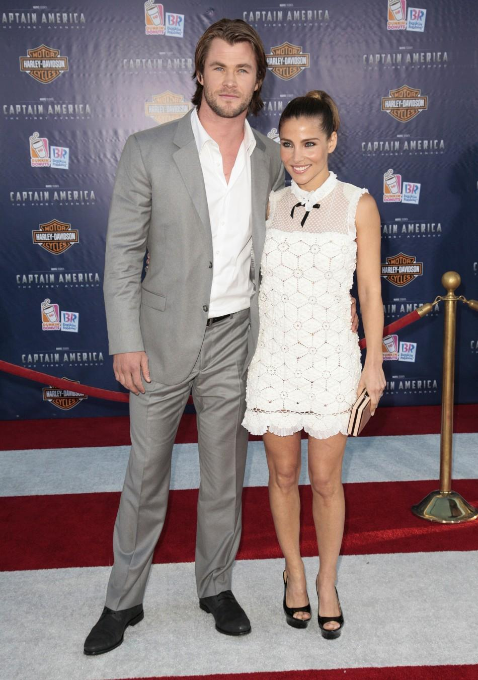"""Actor Hemsworth and his wife pose as they arrive at the """"Captain America: The First Avenger"""" film premiere in Hollywood"""
