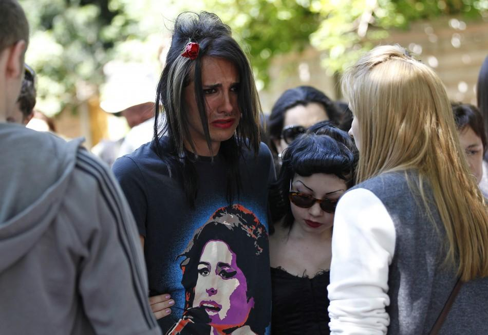 Fans react as they gather outside the home of Amy Winehouse in London