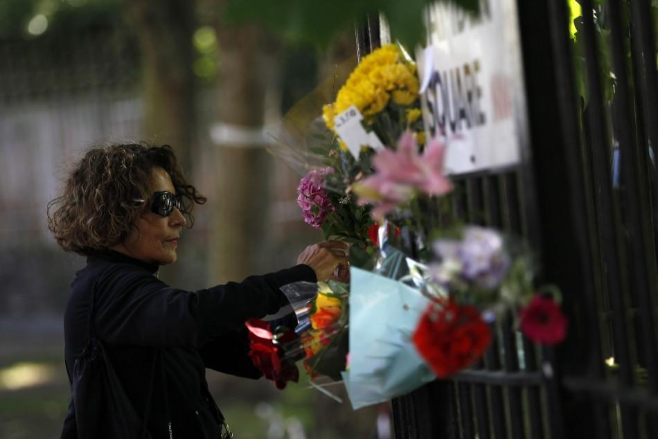A woman leaves flowers outside the home of Amy Winehouse in London