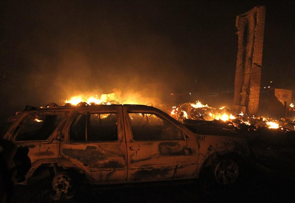 A burnt car sits in front of a house that has been razed to the ground as a wildfire burns out of control near Bastrop, Texas September 5, 2011