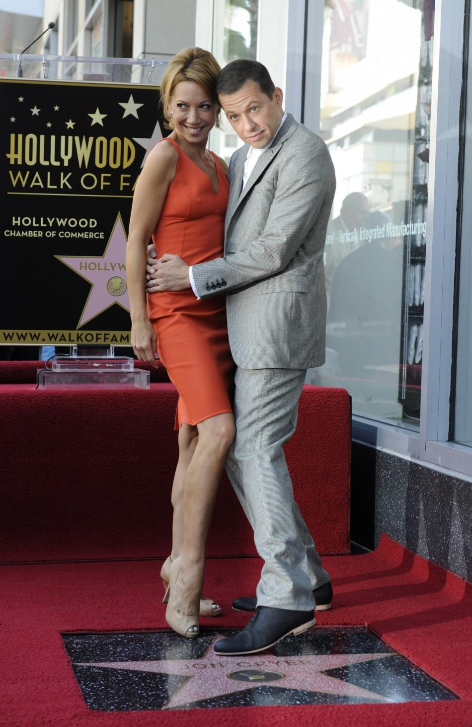 Jon Cryer (R) and his wife Lisa Joyner pose for photographers during a ceremony honoring Cryer with a star on the Hollywood Walk of Fame in Los Angeles