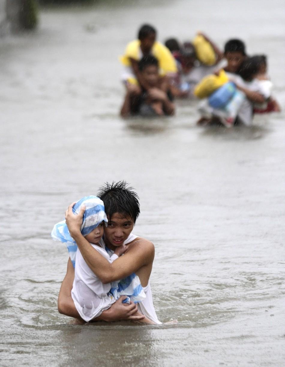 A resident carries his son while crossing on waist deep floodwaters brought by Typhoon Nesat, locally known as Pedring, that hit the Tanza town of Malabon city 27/09/2011