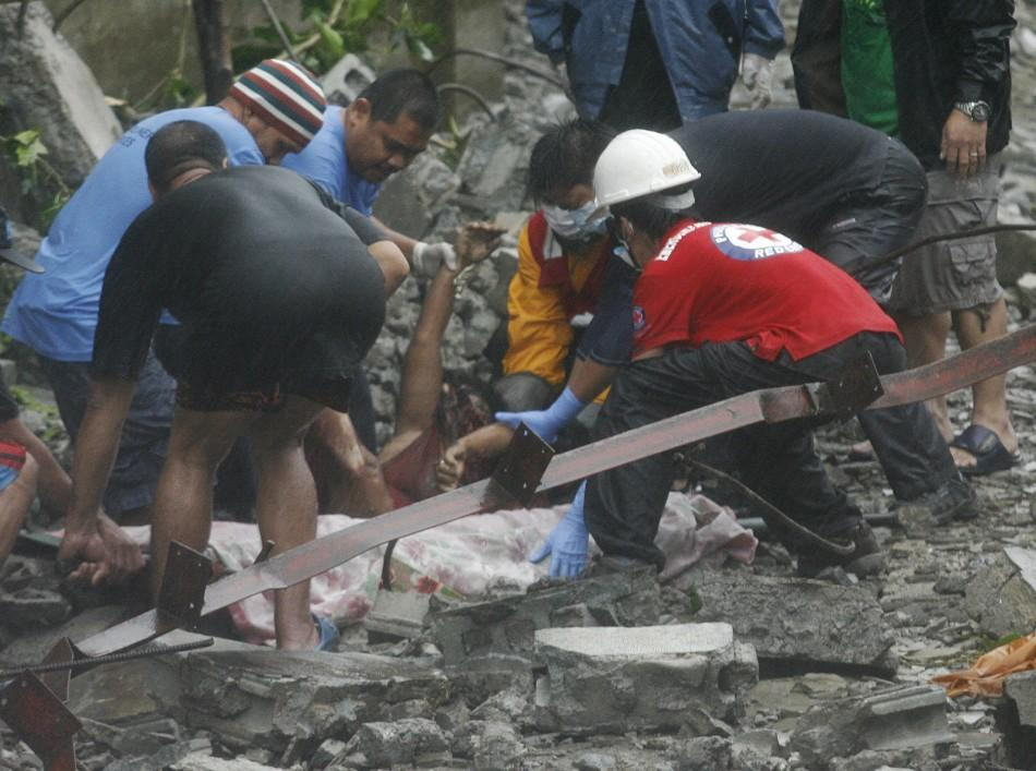Rescuers recover a body beneath the rubble after strong winds brought by Typhoon Nesat knocked down a wall killing four residents in Valenzuela City 27/09/2011