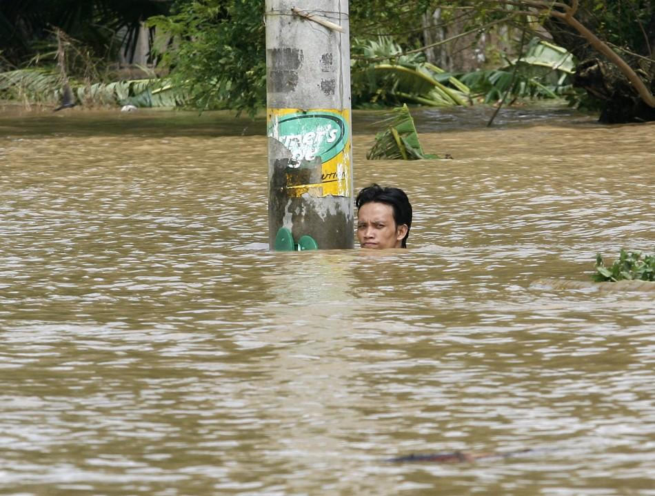 A resident holds onto an electrical post as he takes a rest from swimming in floodwaters brought by Typhoon Nesat in Apalit Pampanga, north of Manila September 29, 2011.