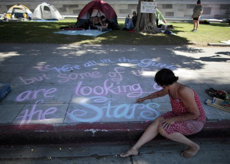 Susan Cameron, 49, writes messages in chalk on the sidewalk at the Occupy LA protest camp in Los Angeles, California