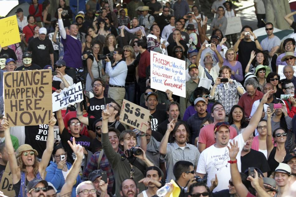 Occupy LA demonstrators cheer on the lawn in front of Los Angeles City Hall