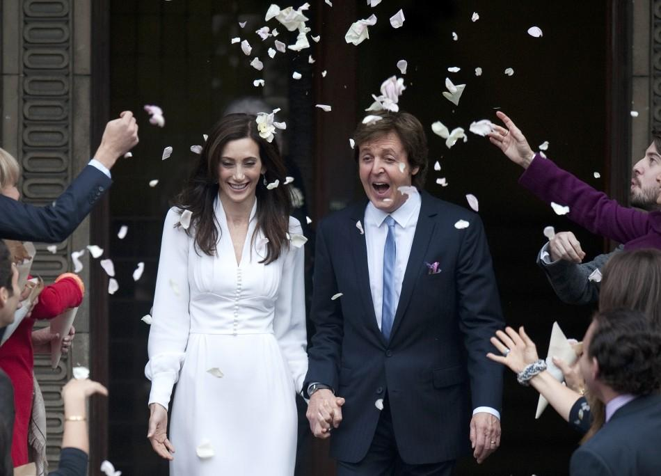 Singer Paul McCartney and his bride Nancy Shevell are showered in confetti as they leave after their marriage ceremony at Old Marylebone Town Hall in London