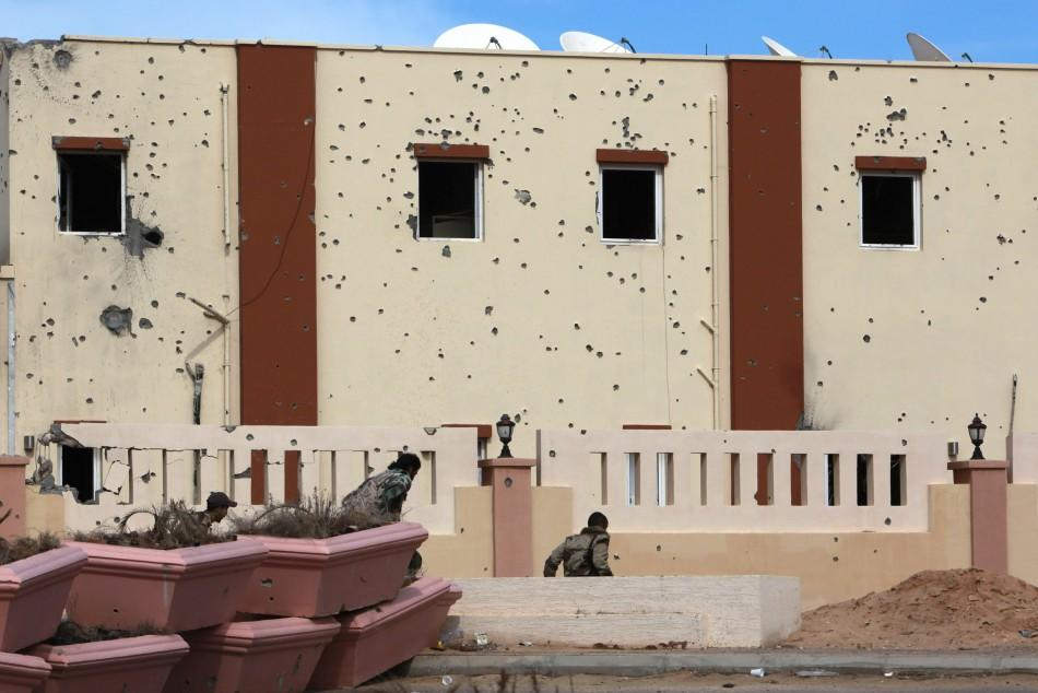 Anti-Gaddafi fighters take cover while running in a street in Sirte during clashes with pro-Gaddafi forces