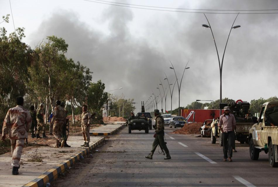 Anti-Gaddafi fighters stand guard at an area that they have taken control as their forces capture main landmarks in Sirte