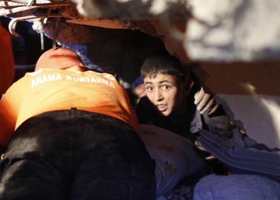 Yunus, a 13-year-old earthquake survivor, waits to be rescued from under a collapsed building by rescue workers in Ercis, near the eastern Turkish city of Van, early October 24, 2011.