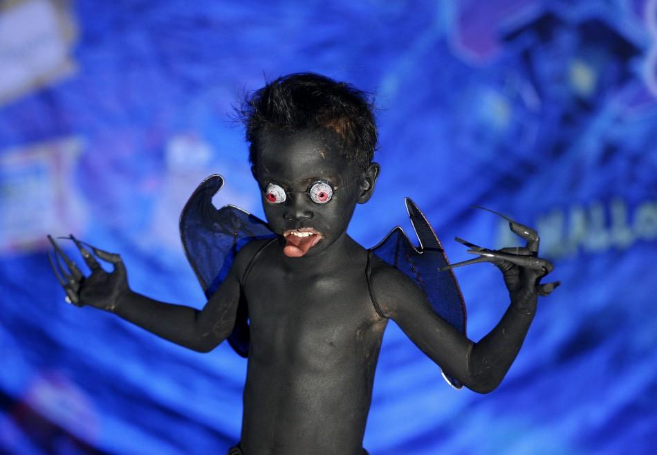 "A boy models his monster costume during the kids costume competition at the ""Scaredy Cats and Dogs"" Halloween fund-raising event at a mall in Quezon City, Metro Manila, October 23, 2011."