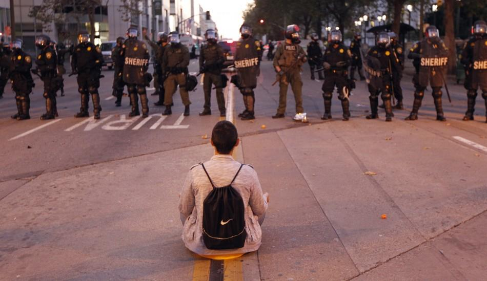 A man sits in front of a police line at City Hall during an anti-Wall Street protest in Oakland, California