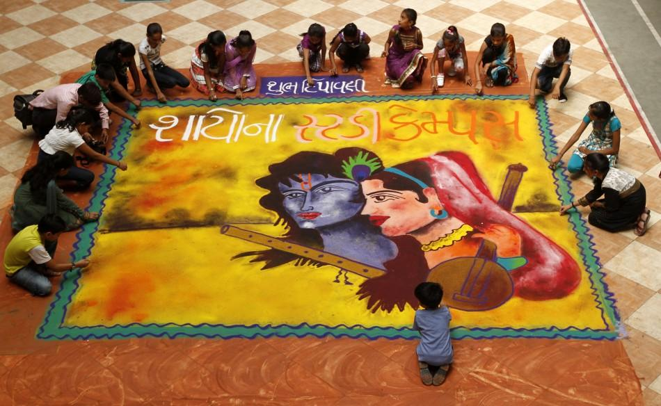 "Students put finishing touches to a ""rangoli"", or mural made out of coloured powders, at a school ahead of Diwali festival celebrations in Ahmedabad on October 21, 2011."