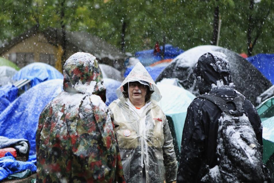 Members of the Occupy Wall Street movement discuss the weather while standing in Zuccotti Park during the first snow fall of winter in New York October 29, 2011.
