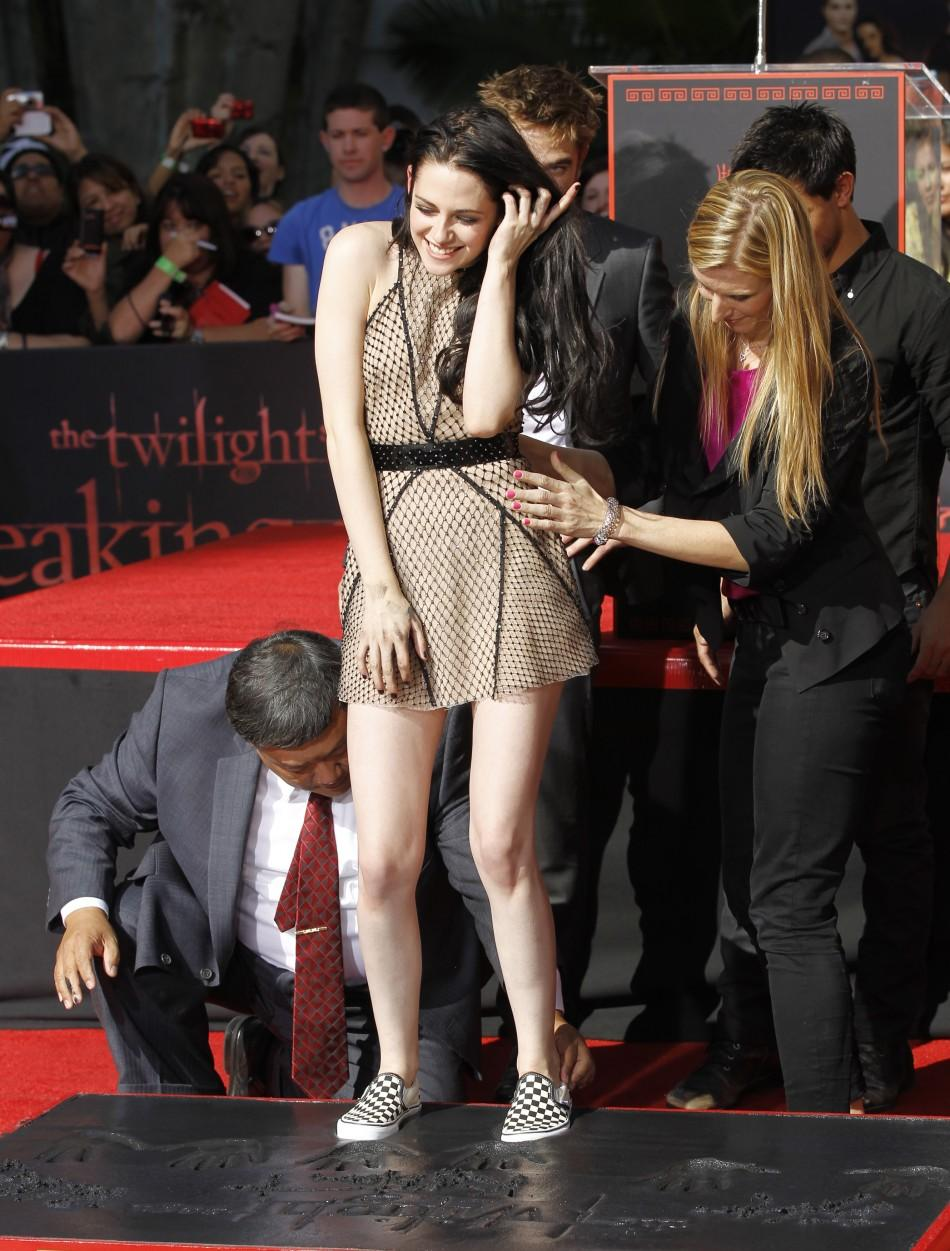 Actress Kristen Stewart puts her footprints in cement during a hand and footprint ceremony at the Grauman's Chinese Theatre in Hollywood, California