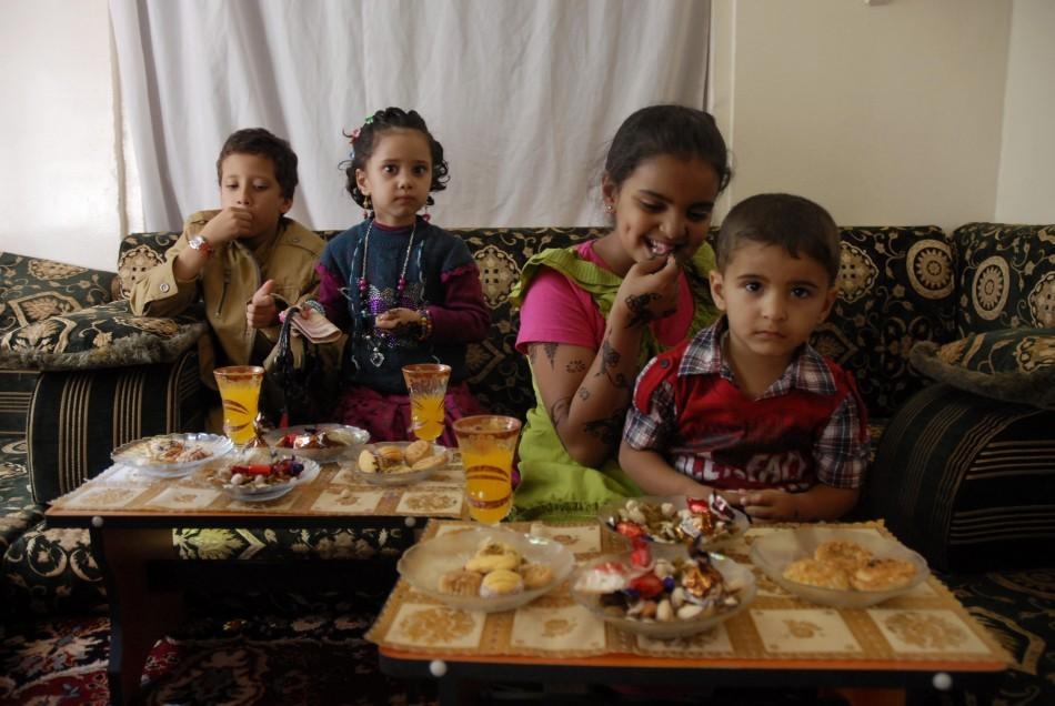 Children wearing new clothes eat candy and cakes on the first day of Eid al-Adha in in Sanaa November 6, 2011.