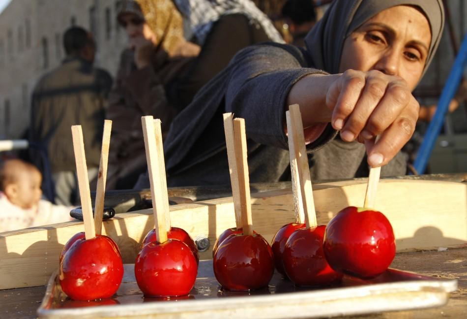 A street vendor arranges apples dipped in a syrup during the first day of Eid al-Adha, at the port-city of Sidon, southern Lebanon, November 6, 2011.