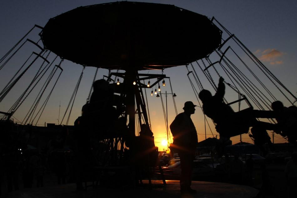 Children ride on a swing carousel during the first day of Eid al-Adha, at the port-city of Sidon, southern Lebanon, November 6, 2011.
