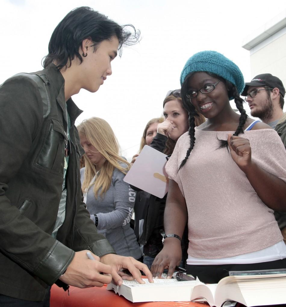 """Actor Booboo Stewart (L) signs autographs as several cast members visit fans camping out for the premiere of """"The Twilight Saga: Breaking Dawn Part - 1"""" in Los Angeles, California"""