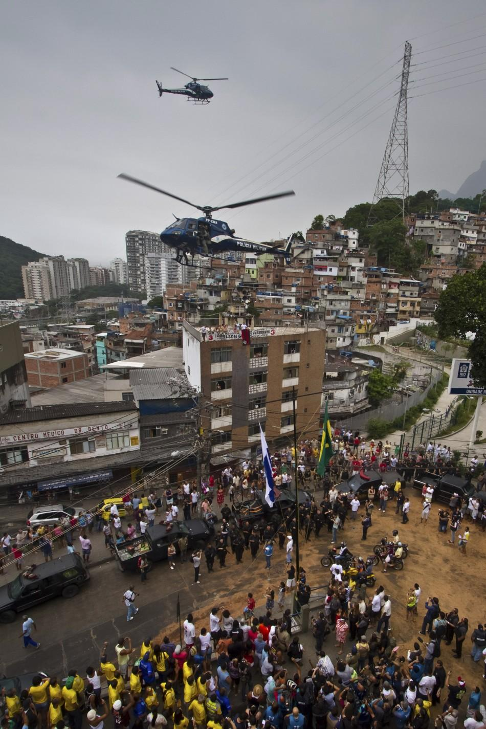 "Police helicopters fly over Rocinha slum during the ""Shock of Peace"" operation to install a Peacekeeping Unit (UPP) in Rio de Janeiro November 13, 2011."