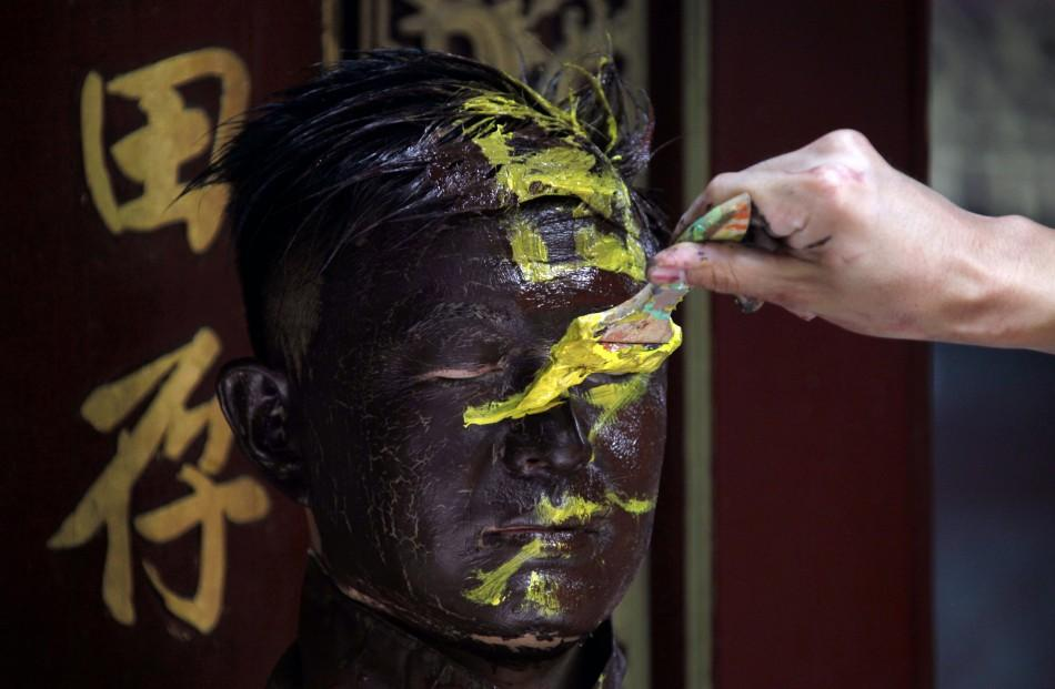 Artist Liu is painted by assistants as