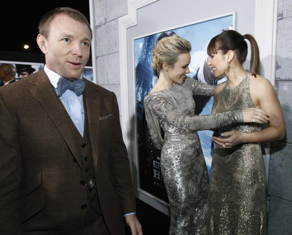 "Cast members Rachel McAdams (C) and Noomi Rapace greet each other, as director of the movie Guy Ritchie (L) stands nearby, at the premiere of ""Sherlock Holmes: A Game of Shadows"" at the Village theatre in Los Angeles, California"