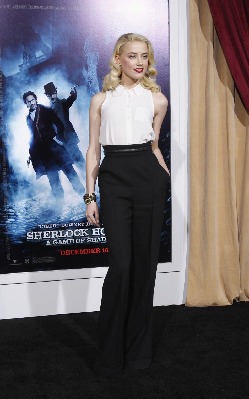 "Actress Amber Heard poses at the premiere of ""Sherlock Holmes: A Game of Shadows"" at the Village theatre in Los Angeles, California"