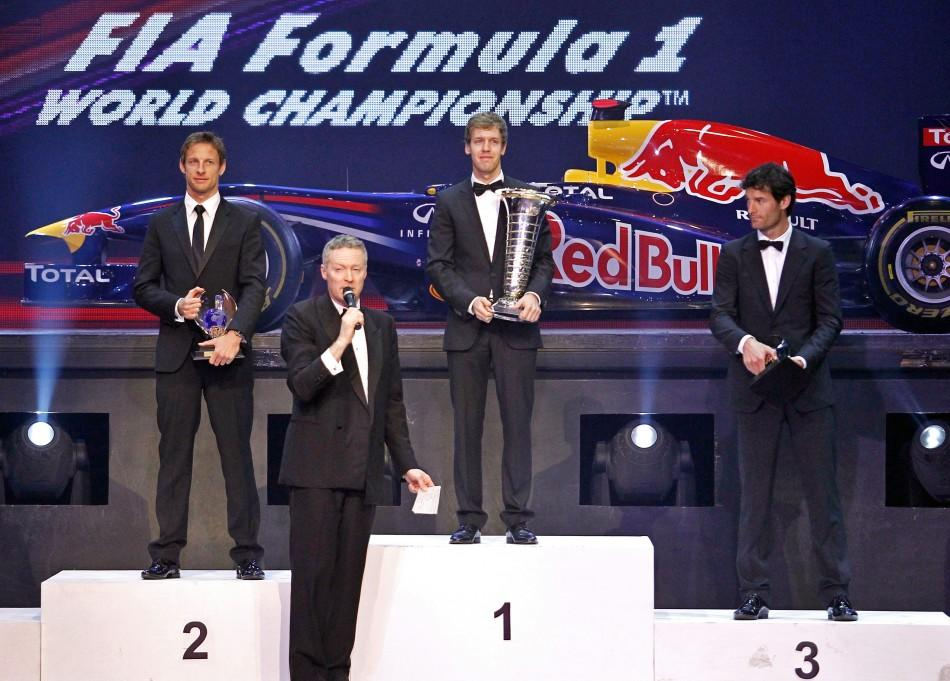 Red Bull Formula One driver Sebastian Vettel (C) of Germany, his teammate Mark Webber (R) of Australia and McLaren Formula One driver Jenson Button (L) of Britain stand on the podium while holding their trophies as an official speaks