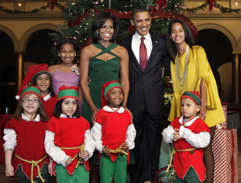 "U.S. President Barack Obama, first lady Michelle Obama and their daughters Sasha (L) and Malia pose with children, dressed as elves, at the ""Christmas in Washington"" celebration at the National Building Museum in Washington"