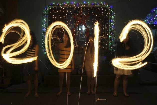 "Women use sparklers to draw ""2012"" for photographers, in front of a house, as they celebrate New Year's Eve in Manila December 31, 2011."