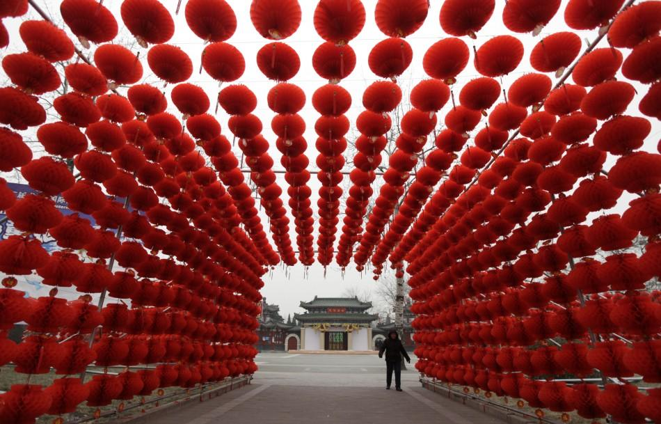A woman walks past red lanterns, which were put up as decoration for an upcoming temple fair, at an entrance of Longtan park in Beijing