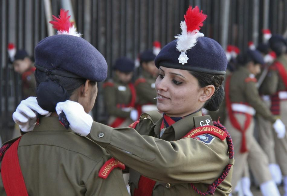 An Indian policewoman adjusts her colleague's dress