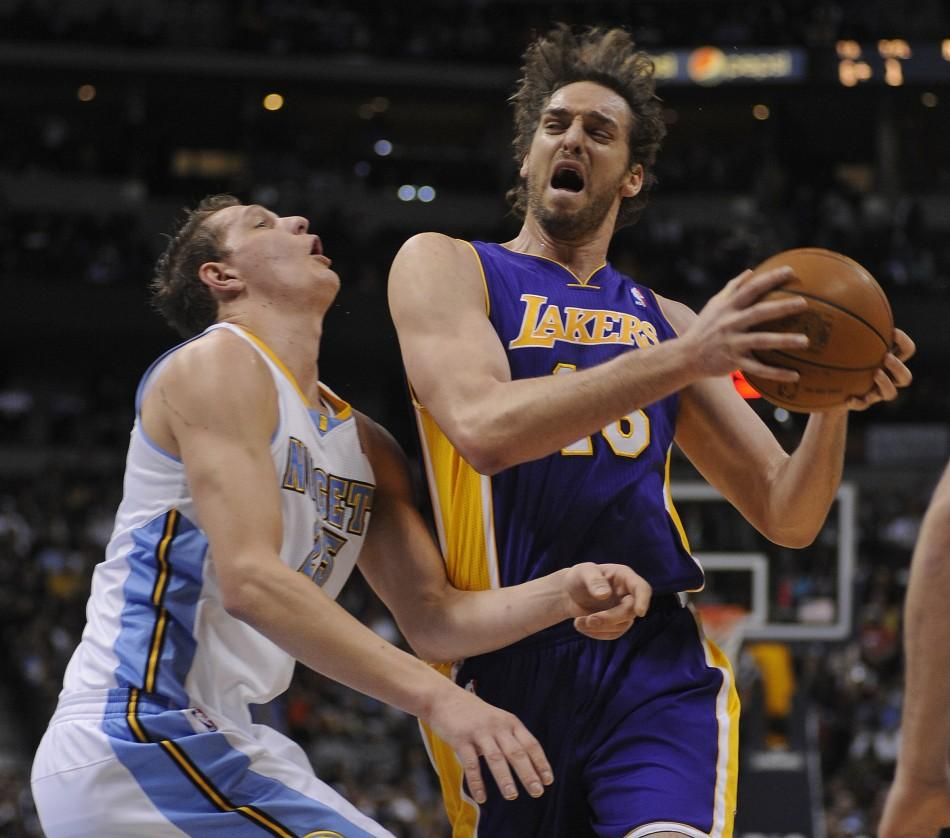 Los Angeles Lakers center Pau Gasol drives to the basket defended by the Denver Nuggets Timofey Mozgov during the first quarter of play in their NBA basketball game in Denver